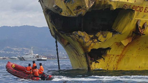 Deadly collision: Coastguard rescuers ride a rubber boat past the damaged bow of the Sulpicio Express 7 cargo vessel.