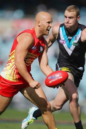 Too quick: Gary Ablett, who was quiet by his standards, beats Port Adelaide's Andrew Moore to the punch.