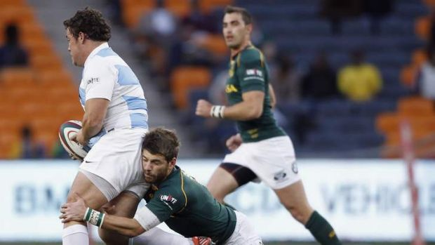 Eusebio Guinazu of Argentina is is ctud down by Sproingboks fullback Willie le Roux.