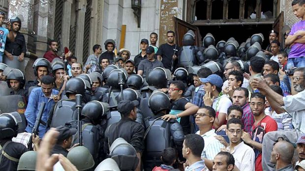 Confrontation: Policemen move into a mosque during clashes with supporters of deposed Egyptian President Mohamed Mursi.