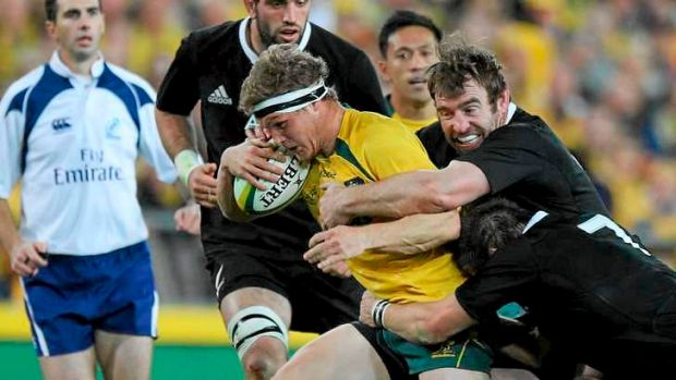 Michael Hooper is wrapped up by the All Blacks powerhouse in Sydney on Saturday night.