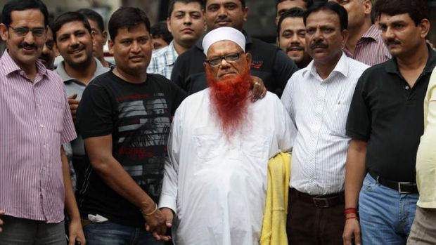 Indian policemen in plain clothes surround Abdul Karim alias Tunda, centre in white cap.