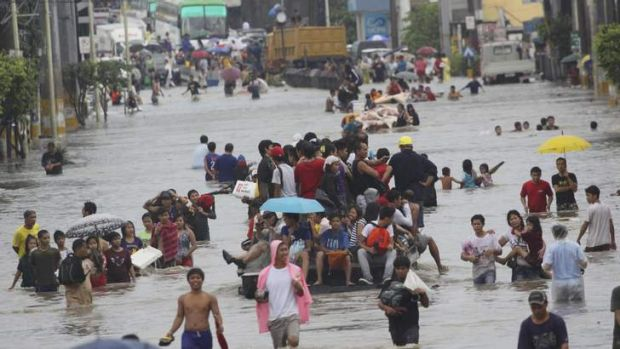 People wade through floodwaters brought by monsoon rain and intensified by tropical storm Trami, in Las Pinas city, ...