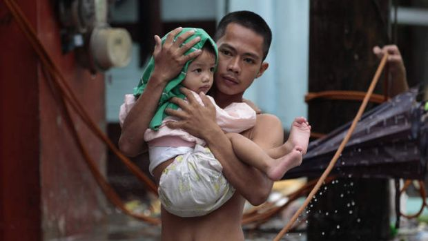 A Filipino man carries his son across a flooded street as they evacuate to higher grounds in Las Pinas, south of Manila.