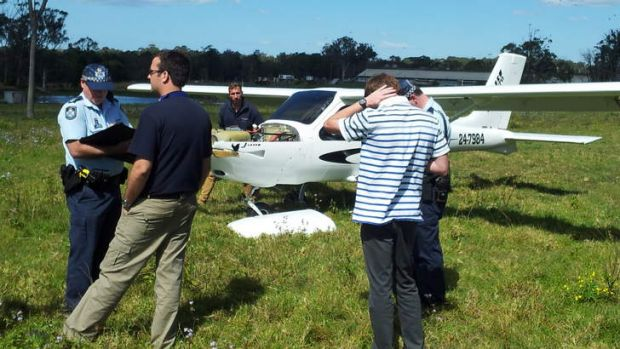 Police and witnesses at a Victoria Point paddock where a light plane made an emergency landing this morning