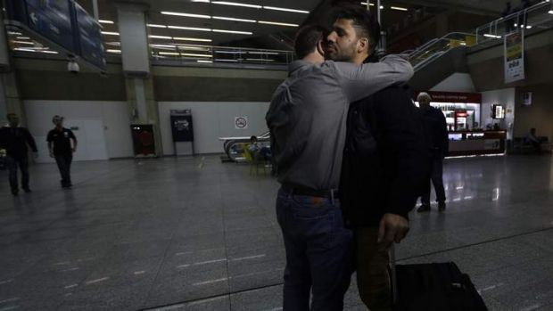 'Security threat': Journalist Glenn Greenwald, left,  embraces his partner David Miranda upon his arrival at Rio de ...