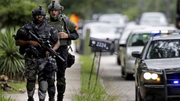 Dekalb County Police SWAT officers run toward Ronald E. McNair Discovery Learning Academy after reports of a gunman ...