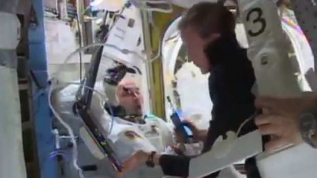 Astronaut Karen Nyberg assists Luca Parmitano after the aborted spacewalk.