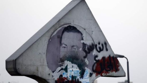 "A defaced picture of former Egyptian President Hosni Mubarak with graffiti that reads, ""Corrupt and deposed"" along a ..."