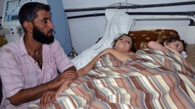 A man sits in a hospital near two children who activists say were affected by nerve gas in the Ghouta region, in the ...