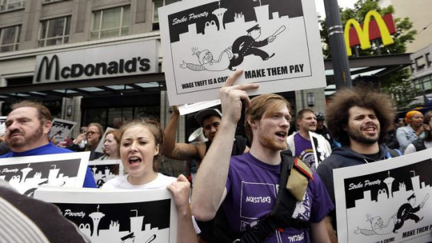 Demonstrators demand higher pay for fast-food workers near a McDonald's restaurant in Seattle.