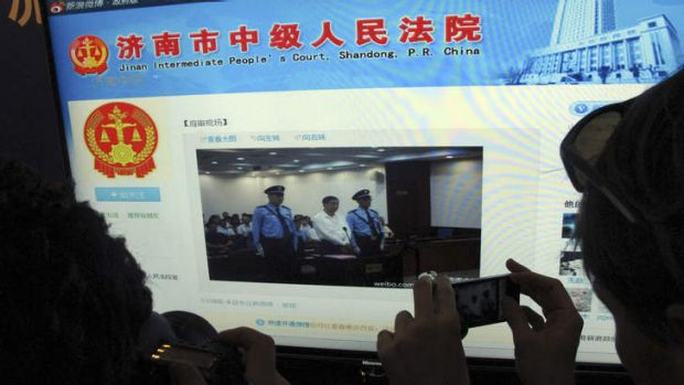 A journalist takes photos of a microblog by Jinan Intermediate People's Court showing disgraced former Chinese ...