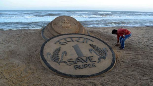 Indian sand artist Sudarsan Pattnaik puts the finishing touches to his sand sculpture of a coin. In just three months, ...