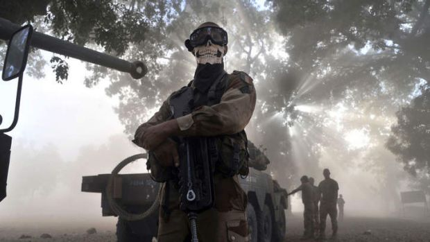 Flashpoint:  A masked French soldier  stands next to a tank in Mali. French troops entered the country to retake control ...