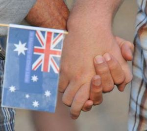 United in grief: Two mourners in Duncan hold an Australian flag bearing Chris Lane's name.