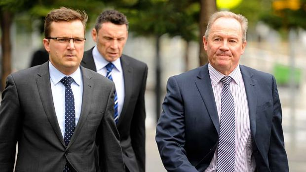 Essendon's football manager Danny Corcoran (right) arrives at AFL House.