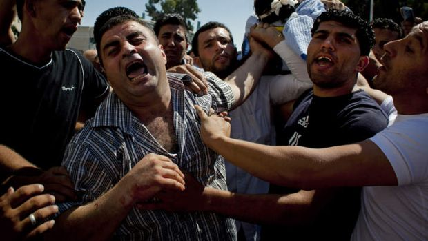 Palestinian mourners carry the body of a 19-year-old man killed in clashes in the West Bank early on Monday.