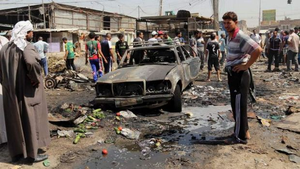 People gather at the site of a car bomb attack in the Iraqi capital of Baghdad.