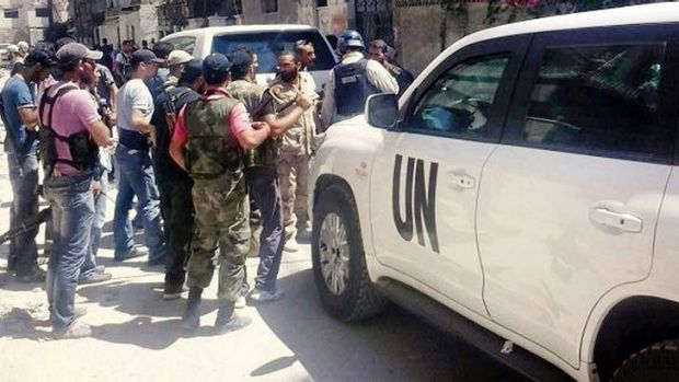Syrian rebels with UN inspectors in Zamalka, east of Damascus. US officials say they expect the inspectors to leave ...