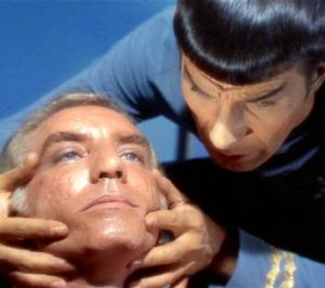"Spock performs a ""mind meld"" in <em>Star Trek</em>."