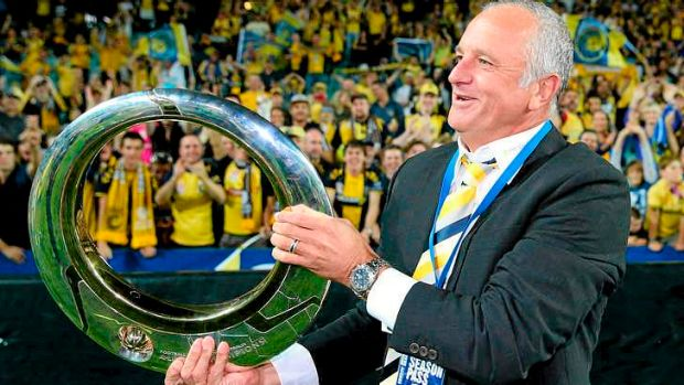 Mariners head coach Graham Arnold celebrates with the A-League trophy.