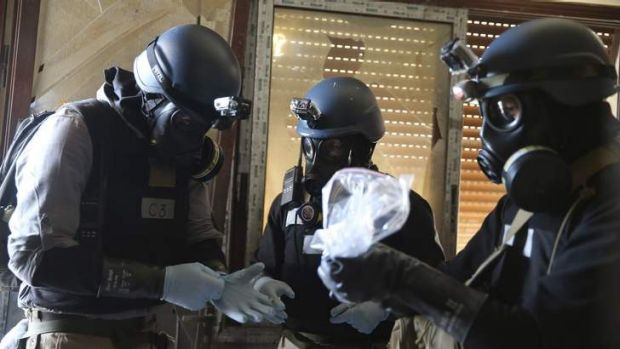A UN chemical weapons expert, wearing a gas mask, holds a plastic bag containing samples from one of the sites of an ...
