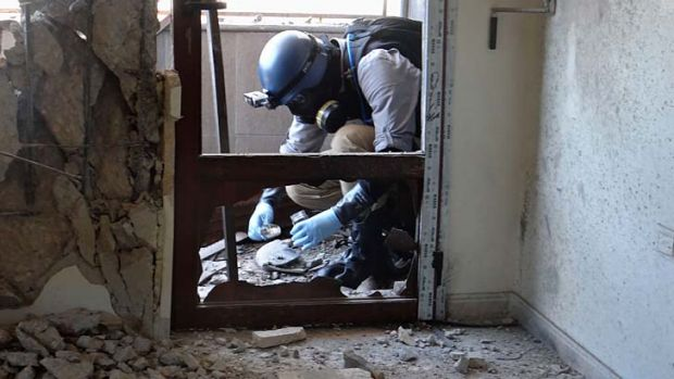 A United Nations arms expert collects samples as they inspect the site where rockets had fallen in Damascus' eastern ...