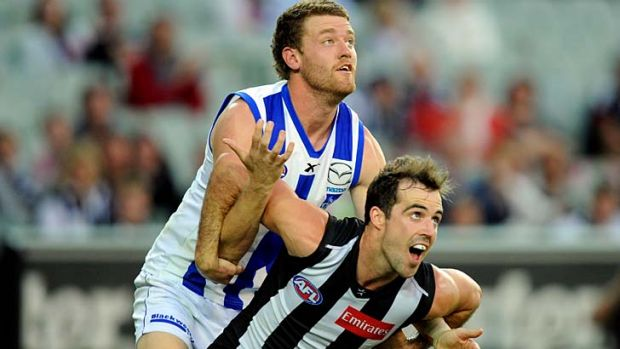 Collingwood's Steele Sidebottom battles with North's Lachlan Hansen.