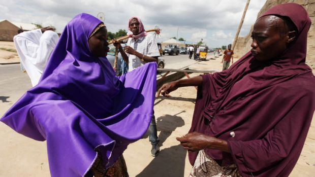 Wary: Habiba Saadu (right), a member of the vigilante force dubbed the Civilian JTF, searches a woman under her veil at ...