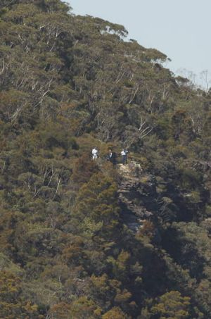 NSW police officers look out over the clifftop near Sublime Point, Leura.