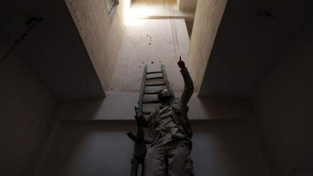 Hope for a strike: A Free Syrian Army fighter, carrying his weapon, climbs a ladder inside a building in Deir al-Zor.