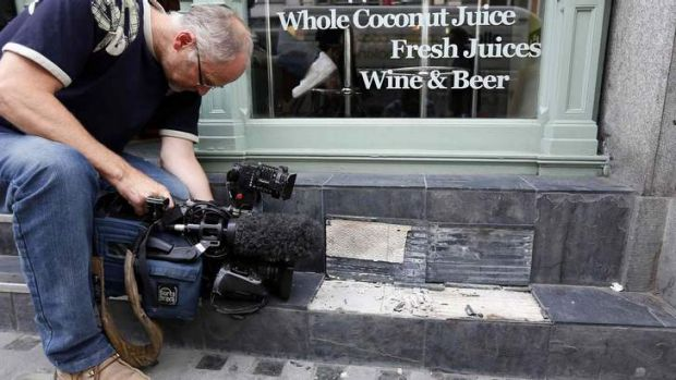 A camera man films broken slates outside a cafe in London. Local media reported the tiles had shattered from sunlight ...
