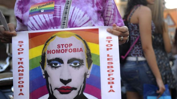 A demonstrator holds a poster depicting Russian President Vladimir Putin with make-up as he protests against homophobia ...