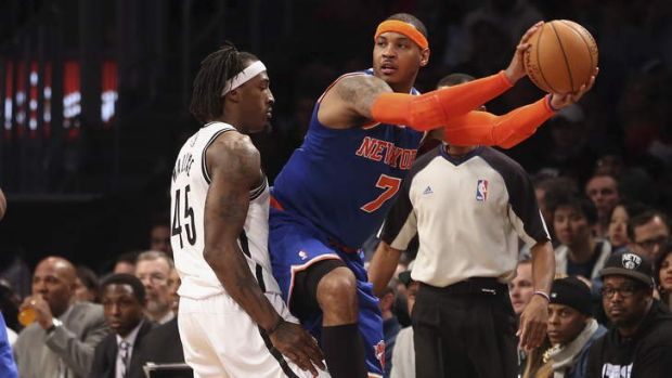 Under the microscope: New York forward Carmelo Anthony looks to pass while Gerald Wallace of the Brooklyn Nets tries to ...