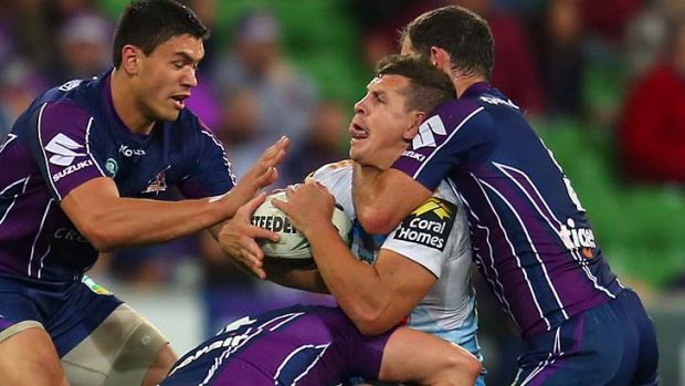 Under the pump: Gold Coast's Greg Bird is set upon by Melbourne Storm players on Saturday night.
