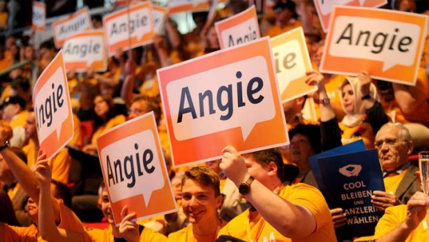 Expected victory: Supporters of Angela Merkel wave posters on Sunday in Dusseldorf.