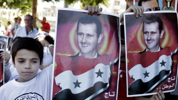 Lebanese boys hold portraits of Syrian President Bashar al-Assad, during a demonstration against a possible military ...