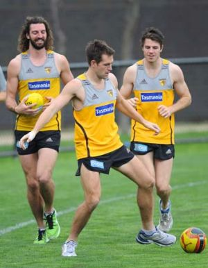 Hawthorn skipper Luke Hodge shows off his soccer skills to teammates Matt Spanger and Isaac Smith at a recovery session ...