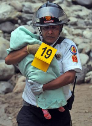 A firefighter carries the corpse of a little child at site of a bus accident  about 65 km west Guatemala City.