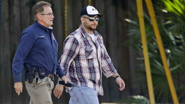 George Zimmerman, right, is escorted by a police officer after a domestic incident was reported.
