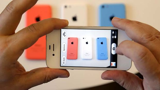 Members of the media review the new iPhone  5c during a new product announcement at Apple headquarters on Tuesday, Sept. ...