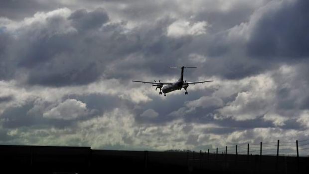 An aircraft coming into land fights the strong cross wind at Canberra Airport.