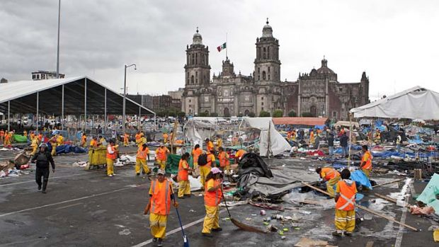 Strikers cleared: City workers begin to clean up the Zocalo.