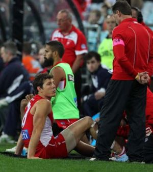 Kurt Tippett talks to Sydney Swans doctor Nathan Gibbs after he was forced to leave the field.