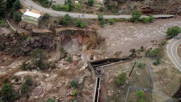 This aerial photo shows a  raging waterfall destroying a bridge along Highway 34 toward Estes Park, Colorado.