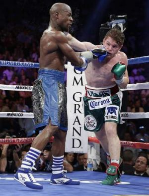 Floyd Mayweather Jr., left, exchanges punches with Canelo Alvarez in the seventh round.