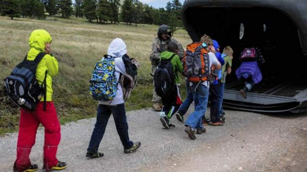 Children board a rescue helicopter flown by the US Air National Guard after severe flooding shut down major roads ...