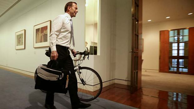 Prime Minister-elect Tony Abbott wheels his bicycle from his old office to his Prime Ministerial office, at Parliament ...