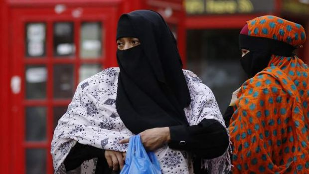 Women wear full-face veils as they shop in London. The British government is struggling with how to better integrate ...