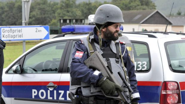 Police stand guard near the villages of Grosspriel and Kollapriel some 90 kms west of Vienna, Austria, on Tuesday, ...